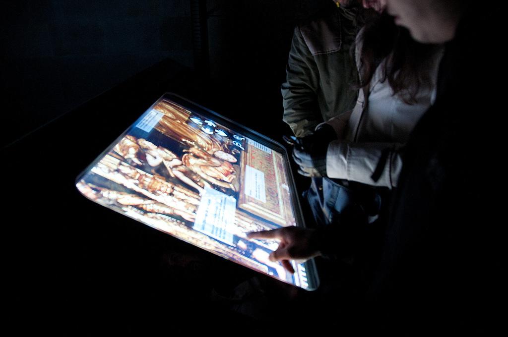 Público interactuando con la pantalla táctil del Retablo Mayor, obra del escultor Forment. Con cada nivel de ampliación, aparece información referenciada a los diversos elementos de la obra. Foto Jordi Hernández.